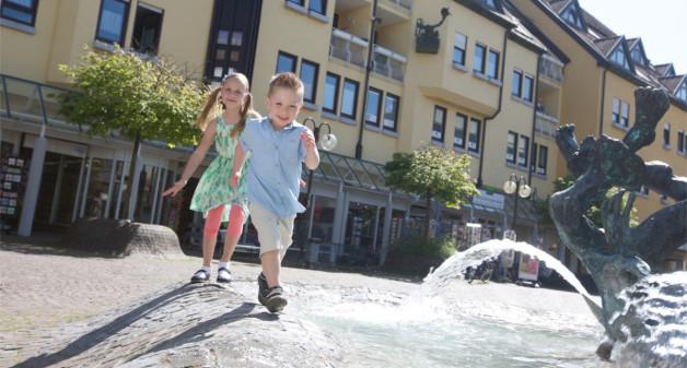 zwei Kinder spielen am Rand eines Brunnen